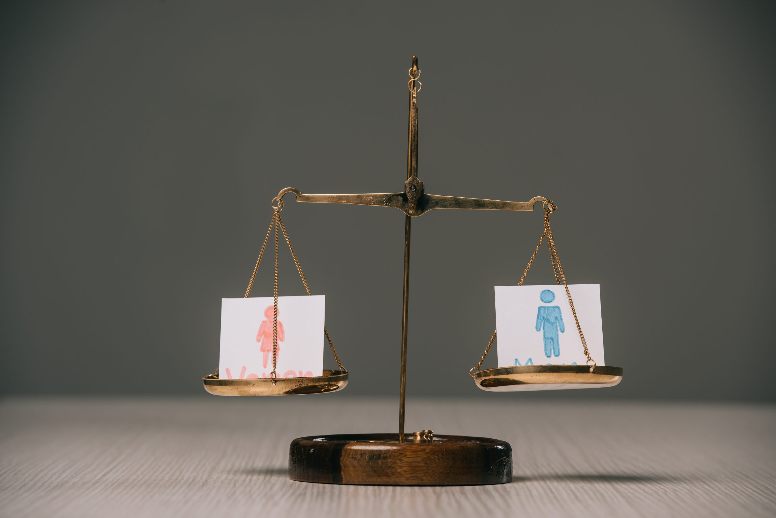male and female symbols on scales on wooden table on grey, gender equality concept